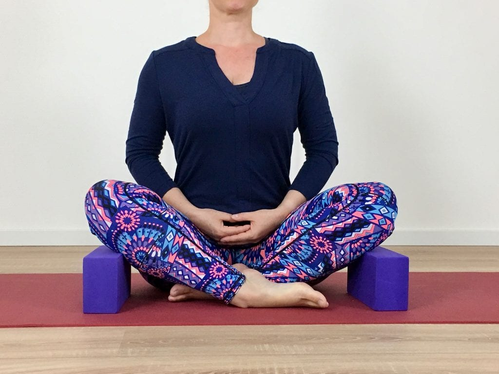 Vlinderhouding - Baddha Konasana - Plaats de blokken in de juiste stand onder de benen zodat het gewicht van de benen niet te veel aan de dijen trekt.
